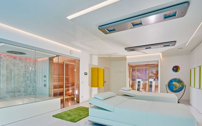 Two of the innovative SWAY pendulum loungers with ceiling-mounted SONNENWIESE® lighting at a first-class wellness-area.