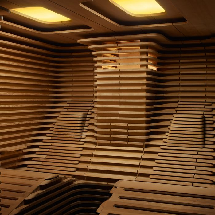 Slatted interior panelling with two curved loungers in the BIORHYTHM design sauna.